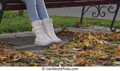 Female feet in white boots sneakers on pavement in fall foliage