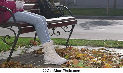 Girl in white boots sitting on the bench wind blows fall foliage