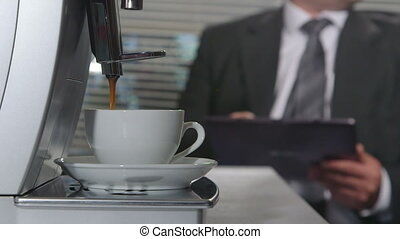 Coffee machine making espresso in office at background business person working