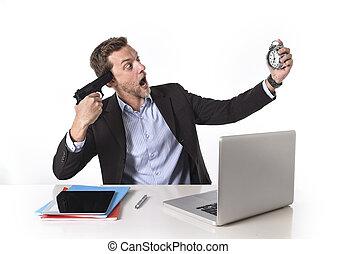 businessman pointing gun to head holding watch in overwork...
