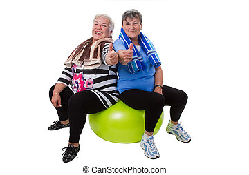 Fitness for senior women - Two senior women sitting on a...