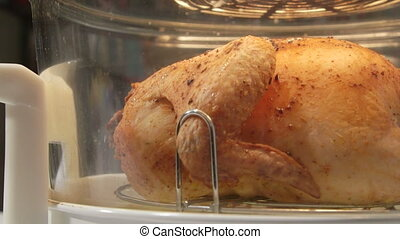Dolly: whole roasted chicken cooking in infrared convection countertop oven close-up