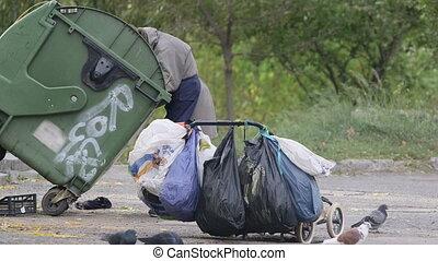 Senior female person dumpster diving on city street