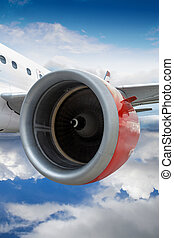 Airplane With Red Engine Flying Through Clouds - Commercial...