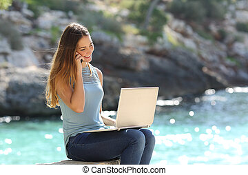 Freelance woman working in vacation on the phone on the...