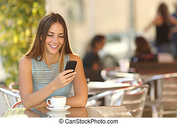 Girl texting on the phone in a restaurant - Girl texting on...
