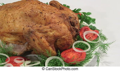 Whole fried chicken with vegetables on white plate pan shot close-up