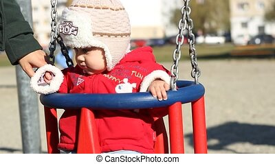 Cold Day Swing Time - Little baby with hat and red jacket,...