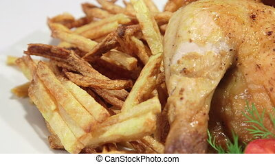 Fried chicken with french fries and tomatoes on white plate panning close-up