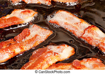Frying Bacon - A bacon cooking detail, slices of bacon in...