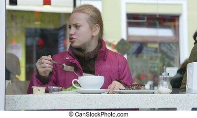 Girl eating light salad at cafe diner on a city street