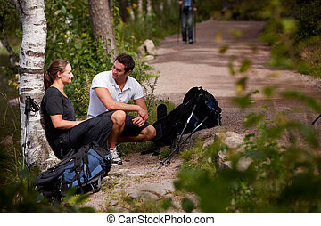 Hiking Break - A couple take a break while backpacking on a...