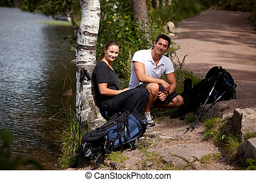 Camping Couple - A couple taking a break while on a hiking...