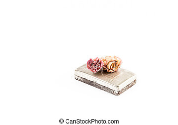 Old rusty tobacco box with two roses on top