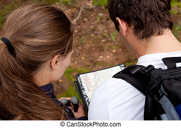 Orienteering Couple - A couple orienteering with a map while...