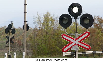 Sign of railway level crossing with flashing signal lights