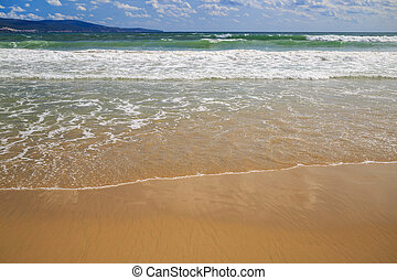 Sea surf closeup - Surf on a sandy beach Wet sand Focus on...