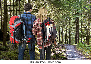 Backpacking couple in a forest - young couple with backpacks...
