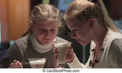 Two girls using tablet computer and drinking cappuccino at...