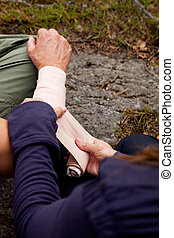 Arm Bandage - A woman applying an arm bandage on a male...