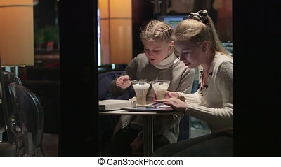 Teenage girls with tablet computer seen through the window of a coffee shop