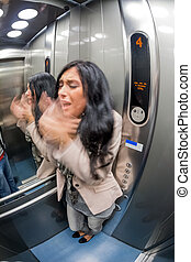 woman with claustrophobia in elevator - a young woman with...
