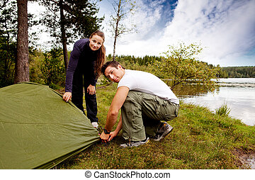Camping Man and Woman - A man and woman camping - setting up...