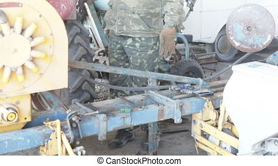 Mechanics working people walking near the tractor mechanisms