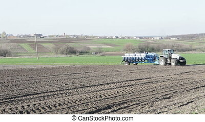 tractor leaving the field with a drill - SMELA,...