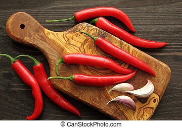Pepper and garlic - Red peppers and garlic on a wooden...