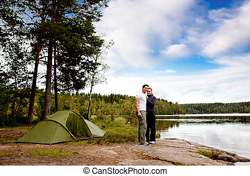 Camping by Lake - A couple of happy campers by a lake and...