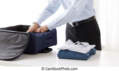 businessman packing clothes into travel bag