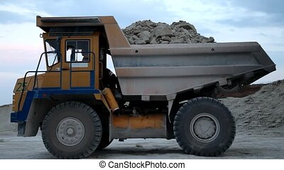 Heavy mining dump truck being loaded with iron ore