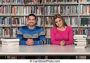 Portrait Of A Student Couple Studying At Library - Group Of...