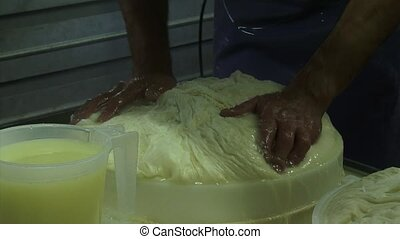 Cheese maker transfers curd mass in cheese mold + whey -...