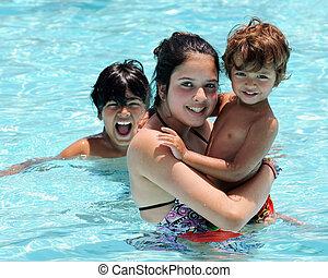 Sibling Swim - Three biracial siblings having fun in a...