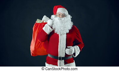 Festive Times - Santa Claus with sack of gifts heaving with...