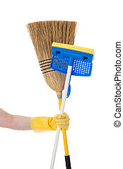 Hand holding a mop and a broom - Household chores - A yellow...