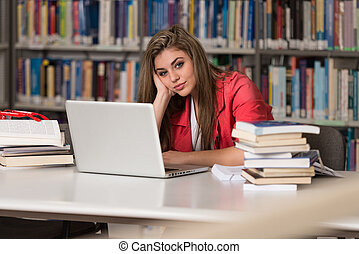 Confused Female Student Reading Many Books For Exam -...