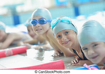 group of happy kids children at swimming pool class learning...
