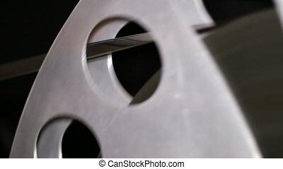 35mm Film Cinema Reel Rewinding - A technician rewinds 35mm...