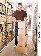 Delivery Man With Stacked Cardboard Boxes In Warehouse