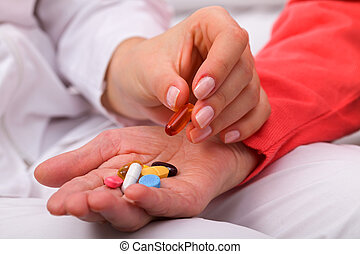 Elderly care - Elderly woman holding pills in her wrinkled...