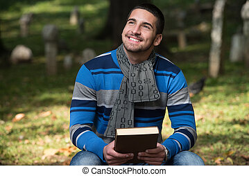Handsome Young Man Reading A Book In The Park - Portrait Of...