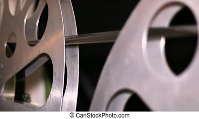 35mm Film Cinema Reels Rewinding - A technician rewinds 35mm...