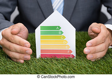 Businessman Protecting Energy Consumption Label On Grass -...