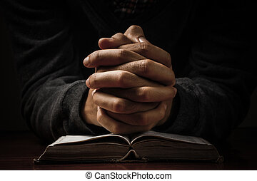 Praying Hands With Bible - Hands of a man praying in...