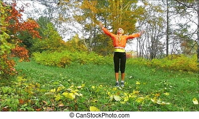 happy  woman throwing fall leaves