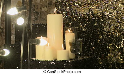 Lighted candles on draperies with sequins - Lighted candles...