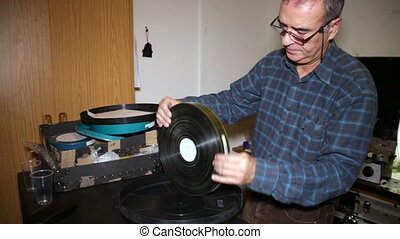 Film Technician Checking Film - A technician takes the film...